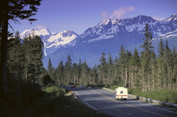 Camper travelling down Alaskan road with mountain view.